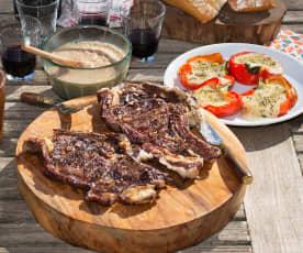 Chuletón a la brasa con salsa de oporto y pimientos con provoleta