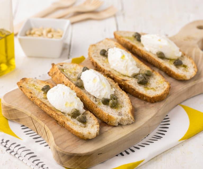 Crostini di pane integrale con crema al caprino, capperi e pinoli