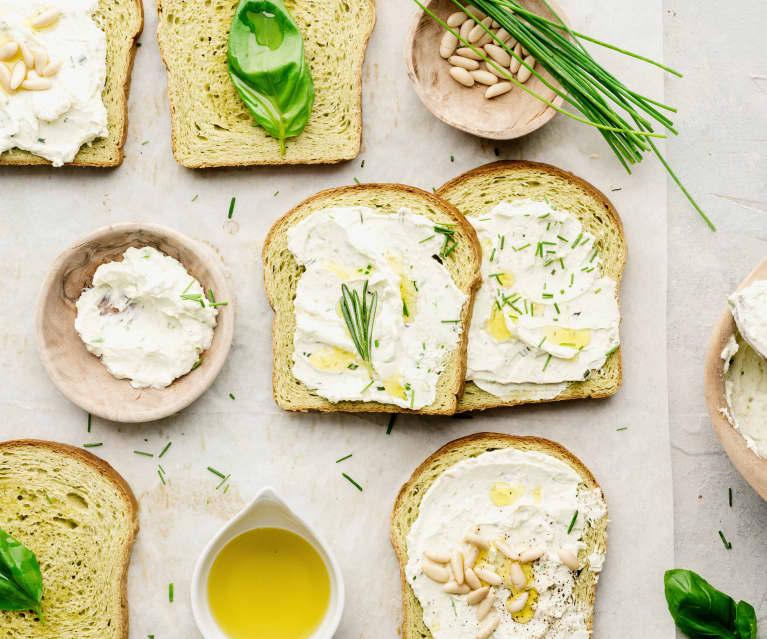 Tostas de pan de albahaca, queso a las hierbas con piñones y aceite de limón